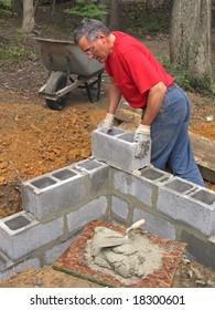 Man laying concrete block wall