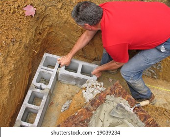 Man laying corner blocks of a foundation wall