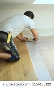 Man laying floor,worker joining parquet floor.