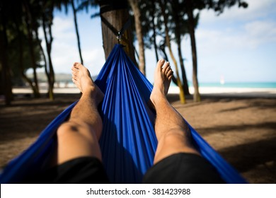Man Laying in Hammock at Wood Line on the Beach. Relaxation concept. Travel concept.