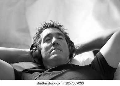 A man laying with hands behind his head, with his eyes closed, while listening to music on headphones