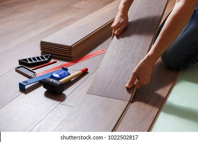 Man laying laminate flooring - closeup on male hands.