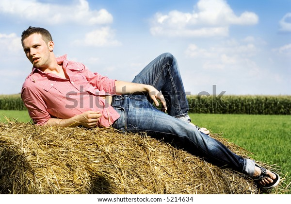 man laying on a haystack