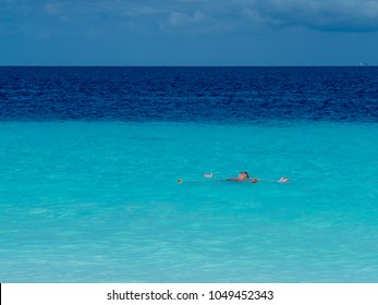 Man laying on his back in blue sea.