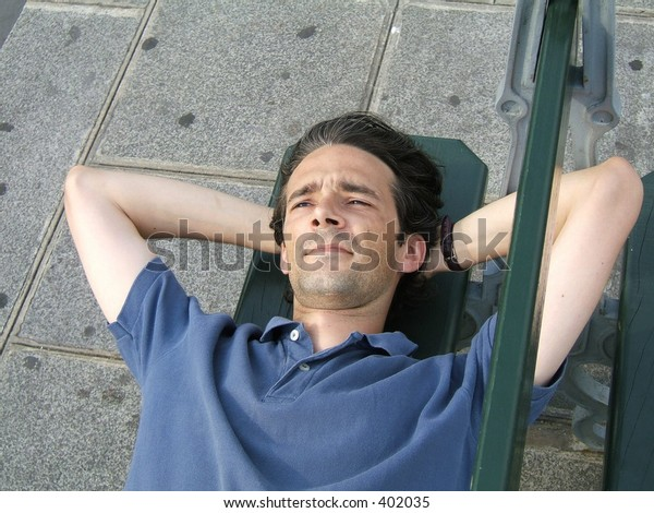 A man laying on a street bench is thinking and smiling