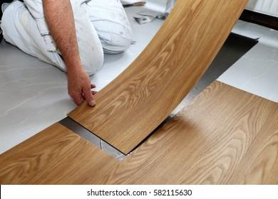 Mann, der PVC-Fußboden legt
