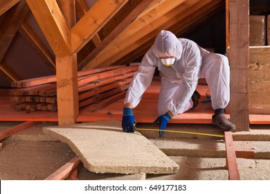Man laying rockwool panels in the attic of a house - measuring the space between wooden scaffolding