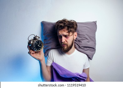 Man laying sad and awake in bed, while looking to alarm clock, sleep disorder. Copy space above head