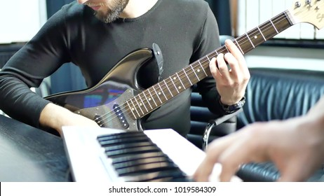 Man lead guitarist playing electrical guitar. Rock band practice play piano. Musician hands playing on electric piano with guitar player. Music band concert