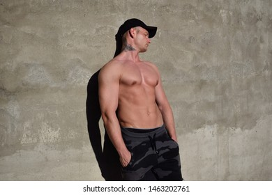 Man leaning against the wall and sunbaths with his eyes closed