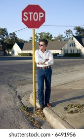 A man leaning leisurely against a stop sign at the corner of a quite intersection.