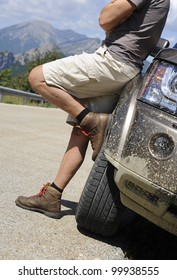 Man leaning on 4x4 vehicle on mountain road in the Pyrenees, Spain