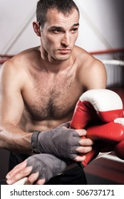 Man leaning on ring rope while holding boxing gloves