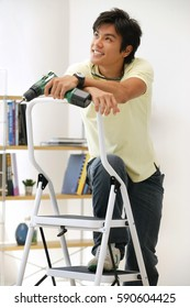 Man leaning on stepladder, holding drill