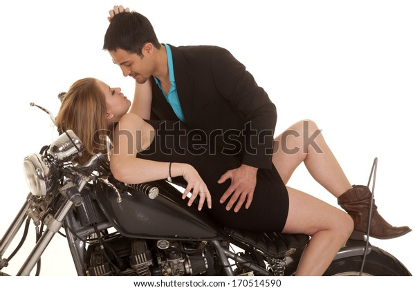 A man leaning over his woman that is laying back on his motorcycle he is holding on to her.