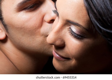 man leaning over kissing woman on cheek