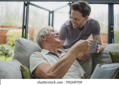 Man is leaning over the sofa to give his father a cup of tea. He is sitting on the sofa and is taking it from him gratefully.