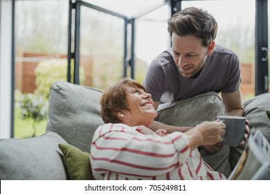 Man is leaning over the sofa to give his mother a cup of tea. She is sitting on the sofa and is taking it from him gratefully.