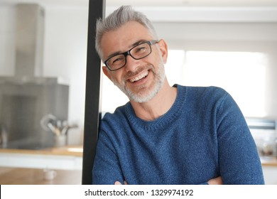 Man leaning and smiling at home in modern kitchen