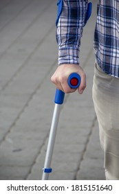 A man leans on an elbow crutch, close-up, selective focus. Concept: support cane for the lame, leg injury.