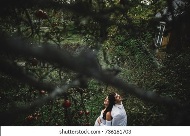 Man leans to pregnant lady tender standing with her in an autumn garden under apple tree