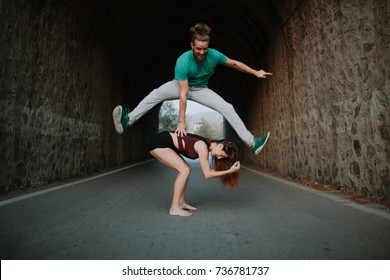 Man leapfrog jumping over woman on a road.