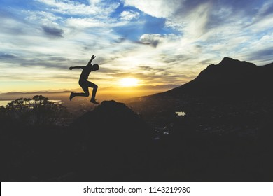 Man Leaping Mid-air on Mountainside