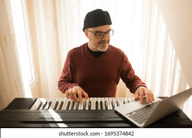A man learning to play piano online with a computer staying at home. Concepts of self taught, staying at home and working online
