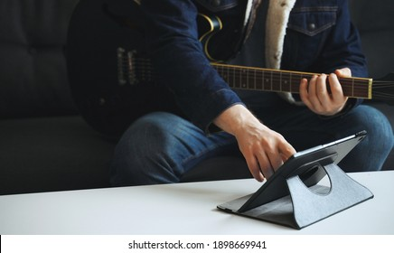 Man learns how to play the guitar. Remote online lesson.