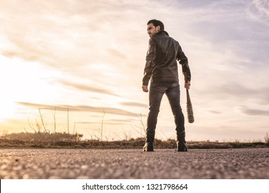 man in leather jacket and baseball bat
