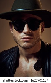 A man in a leather jacket glasses on the face of a hat on his head