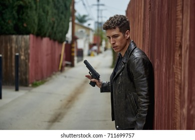 A man in a leather jacket and a gun against a fence in an ally thinking before he steps into action