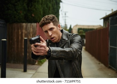 A man in a leather jacket and a gun ready to take out his man