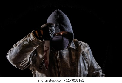 a man with a leather jacket, hood and a bloody knife
