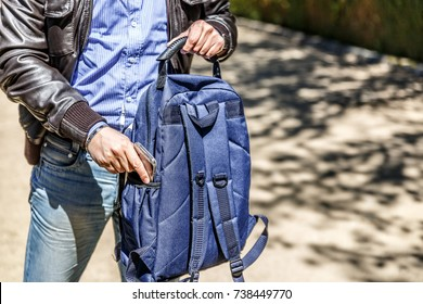 A man in leather jacket and jeans keeps his mobile phone in his blue backpack