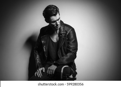 man in leather jacket looks to side while sitting on a stool in studio