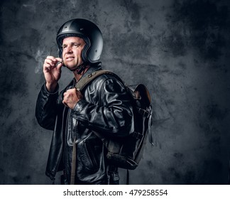 A man in leather jacket and motorcycle helmet smoking a cigarette.