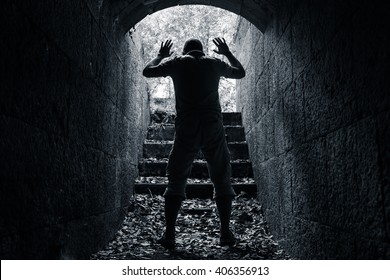 Man leaves dark stone tunnel with raised hands, surrender concept black and white photo