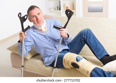 Man with leg in neck brace, knee cages and crutches for stabilization and getting up for rehabilitation