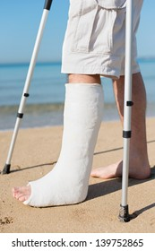 Man with leg plaster at a beach trying to walk