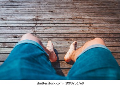Man legs on wooden boardwalk, people relaxing in summer time, first persona view