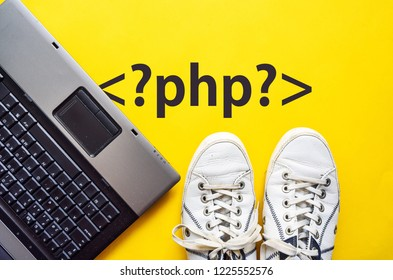 man legs in shoes standing next to laptop and php tag on yellow background