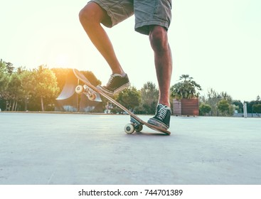 Man legs with skateboard at sunset outdoors - Skater standing on his longboard - Extreme sport concept - Main focus on right shoe - Vsco filter