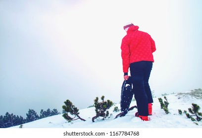 Man legs with snowshoes walk in snow in winter mountains. Detail of winter hike in snowdrift snowshoeing with trekking poles