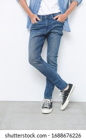 Man legs torn jeans with sneakers on a white background. Isolation on gray background