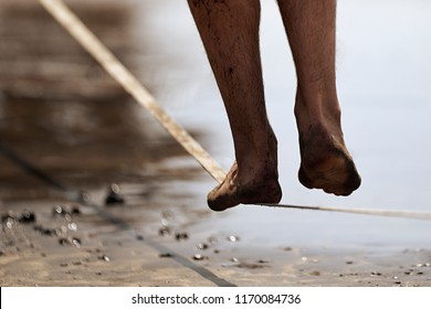 Man legs walk along a tight line in the beach,balances on the slackline close up
