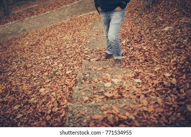 Man legs walking upstairs with autumn leaves