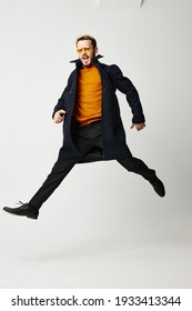 a man with legs wide apart runs forward on a light background and a black coat pants model. High quality photo