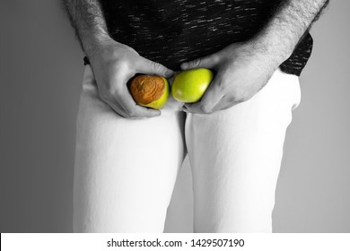 A man at the level of the genitals , holding a ripe and rotten apple. Disease for men. The concept of protection of sexually transmitted infections. Testicular cancer. Close up