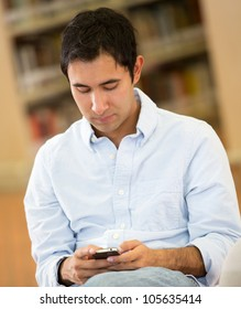 Man in the library texting from his mobile phone